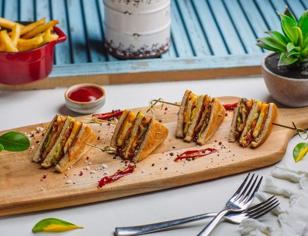 Vier stücke club sandwich auf holzbrett mit pommes frites, ketchup Kostenlose Fotos