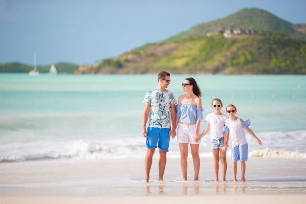 Vierköpfige familie, die auf weißen strand geht Premium Fotos