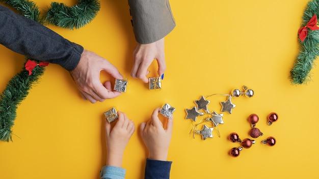 Vierköpfige familie, die mini-geschenke auf gelbem raum mit verstreuten feiertagsverzierungen platziert. Premium Fotos