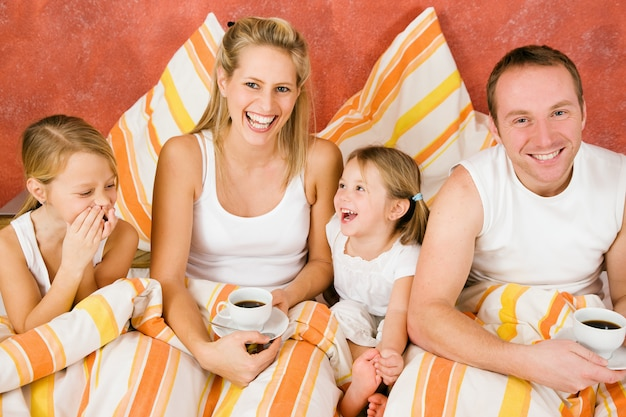 Vierköpfige familie im bett frühstückend Premium Fotos