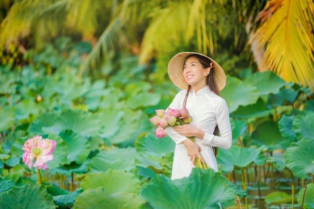 Vietnamesische frauen sammeln den lotos bei sonnenuntergang. Premium Fotos
