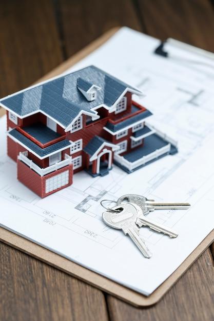 Villa haus-modell, schlüssel und zeichnung auf retro-desktop (immobilien-verkauf-konzept) Kostenlose Fotos