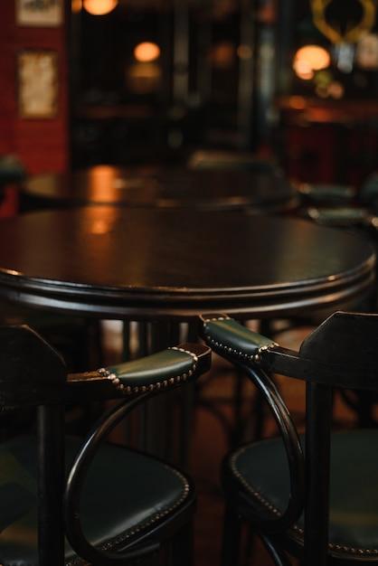 Vintage fasstisch mit zwei vintage hochstühlen, dunklem interieur und dunklen möbeln. Premium Fotos