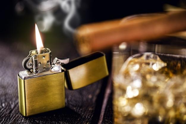 Vintage winddichtes feuerzeug. greifen sie auf zigarre und ein glas alkohol vor Premium Fotos