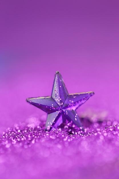 Violetter stern auf einem lila funkelnhintergrund auf einem undeutlichen purpurroten hintergrund Premium Fotos