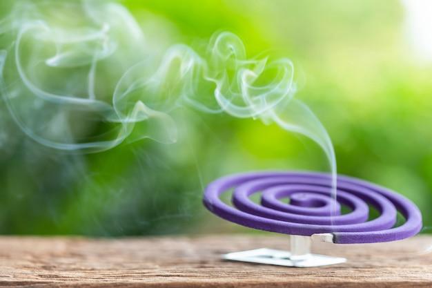 Violettes moskitoabwehrmittel auf holztisch mit grünem unschärfelichtraumhintergrund Premium Fotos