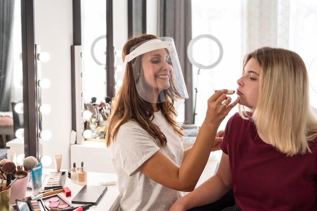 Visagistin mit gesichtsschutz lippenstift auf client setzen Kostenlose Fotos