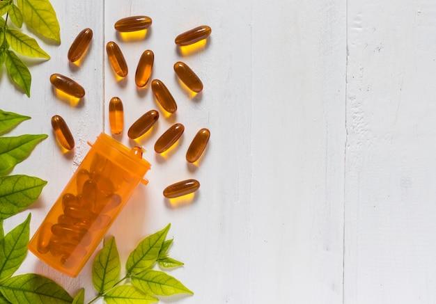 Vitamin d von den fischölkapseln in einer orange flasche auf weißem hölzernem hintergrund Premium Fotos