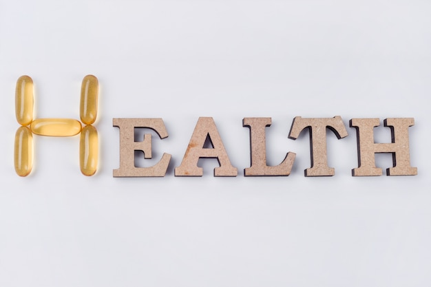 Vitamin e ergänzung, wort gesundheit ist abstrakte holzbuchstaben und kapseln von fischöl. Premium Fotos