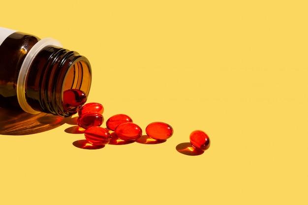 Vitamine auf gelb mit einer braunen flasche Premium Fotos