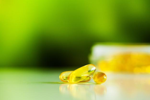Vitaminpräparate, fischöl in gelben omega-3-kapseln. Premium Fotos