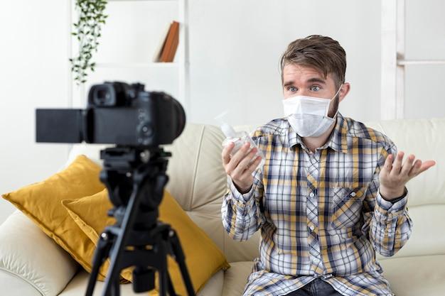 Vlogger videoaufnahme zu hause mit händedesinfektionsmittel Kostenlose Fotos