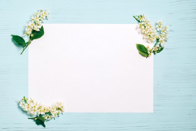 Vogelkirschblütenniederlassung auf weiß und holztisch Premium Fotos