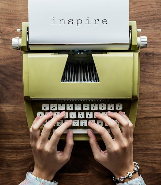 Vogelperspektive eines mannes, der auf einer retro- schreibmaschine schreibt Kostenlose Fotos