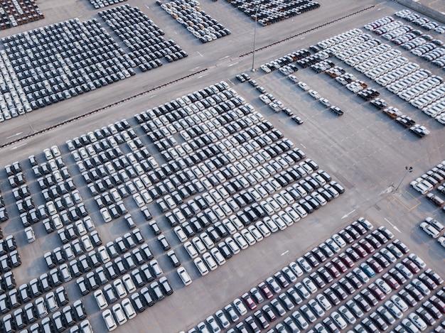 Vogelperspektive von neuen autos parkte am parkplatz der autofabrik. warten auf export und import am internationalen hafen. Premium Fotos