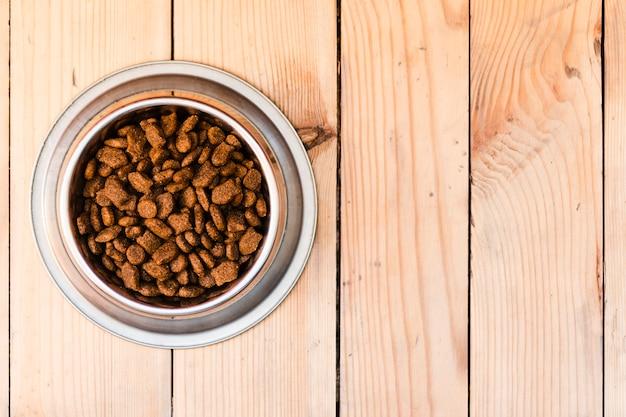 Volle hundenahrungsmittelschüssel auf hölzernem hintergrund mit kopienraum Kostenlose Fotos