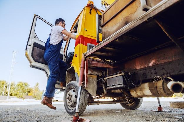 Volle länge des kaukasischen arbeiters in overalls, die bagger betreten. raffinerie außen. Premium Fotos