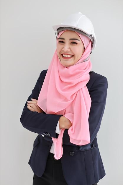 Volle länge erwachsene asiatische muslimische ingenieurin frau im blauen anzug stehend und lachend mit zuversicht Premium Fotos