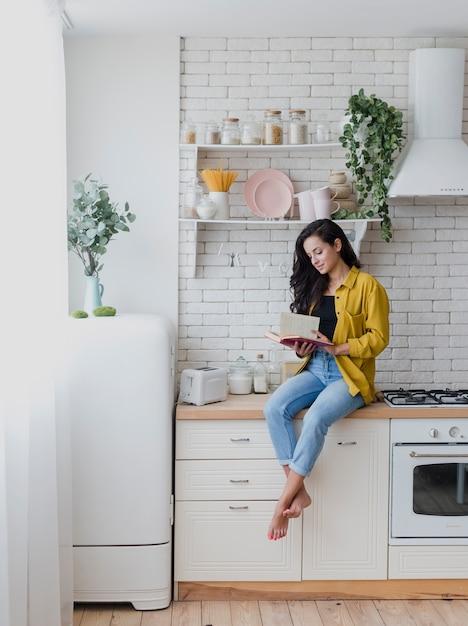 Volle schussfrau, die auf der küchenarbeitsplatte sitzt Kostenlose Fotos