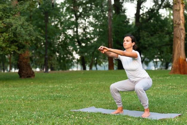 Volle schussfrau, die hocken auf yogamatte tut Kostenlose Fotos