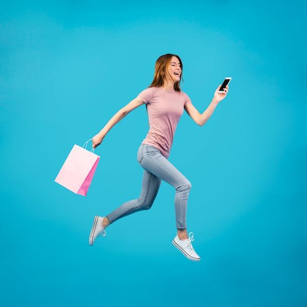 Volle schussfrau, die mit telefon läuft Kostenlose Fotos