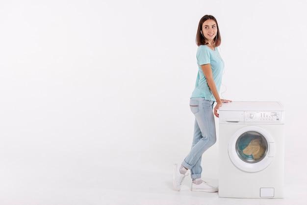 Volle schussfrau, die nahe waschmaschine aufwirft Kostenlose Fotos