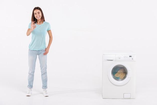 Volle schussfrau, die zustimmung mit waschmaschine ausdrückt Kostenlose Fotos