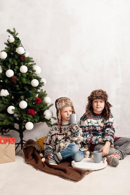Volle schusskinder, die nahe dem weihnachtsbaum sitzen Kostenlose Fotos