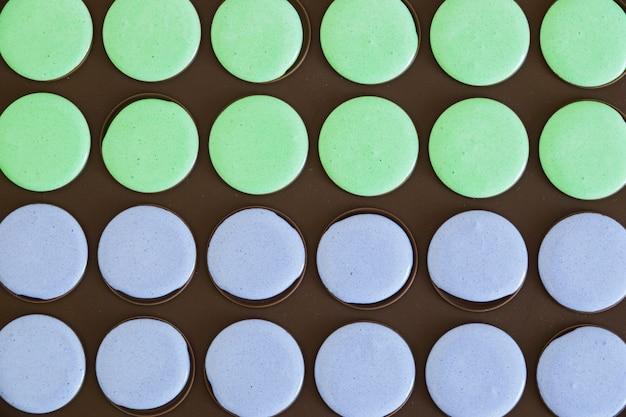 Voller rahmen der grünen und purpurroten makronenmischung im schwarzen backblech Kostenlose Fotos