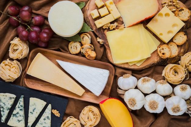 Voller rahmen des klaren käses und der bestandteile mit trauben Kostenlose Fotos