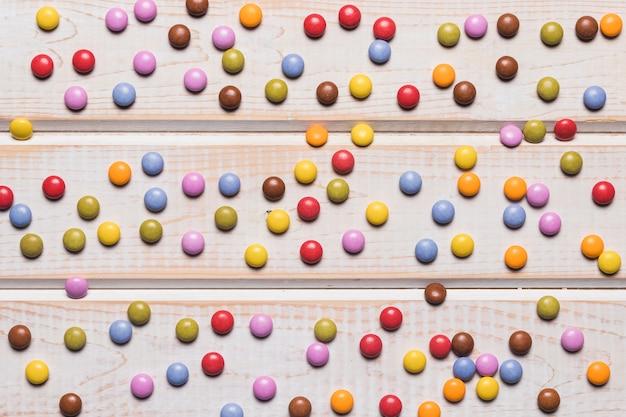 Voller rahmen von mehrfarbigen edelsteinsüßigkeiten auf hölzernem schreibtisch Kostenlose Fotos