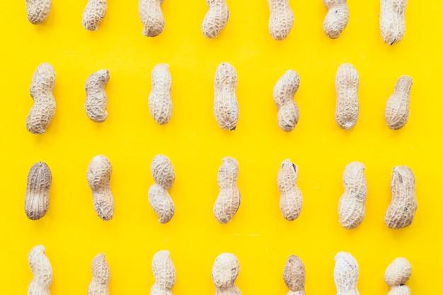 Voller rahmen von rohen ganzen erdnüssen auf gelbem hintergrund Kostenlose Fotos