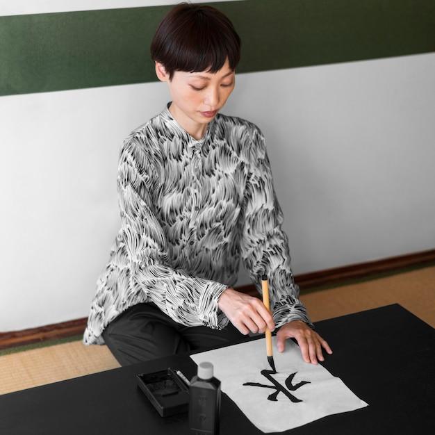 Voller schuss asiatischer frau, der brief malt Kostenlose Fotos
