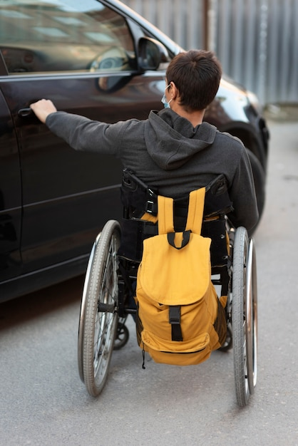 Voller schuss behinderter mann, der autotür öffnet Kostenlose Fotos