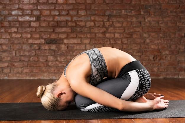 Voller schuss, der frau auf yogamatte sich duckt Kostenlose Fotos