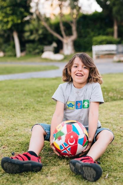 Voller schuss des jungen im gras mit fußball Kostenlose Fotos
