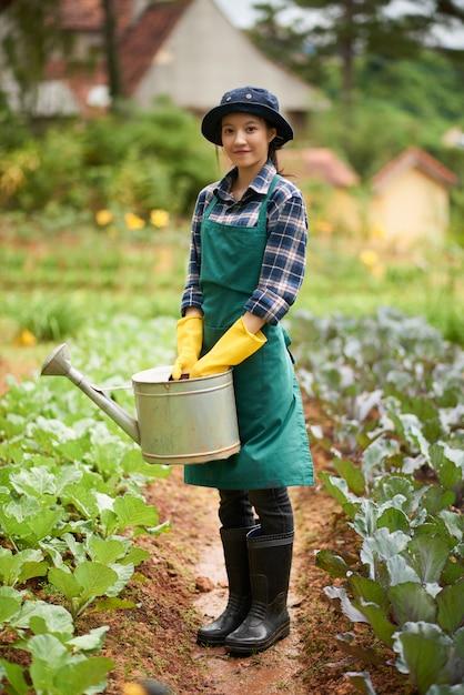 Voller schuss des jungen weiblichen gärtners, der zwischen pflanzenbeeten mit einem trichter steht Kostenlose Fotos