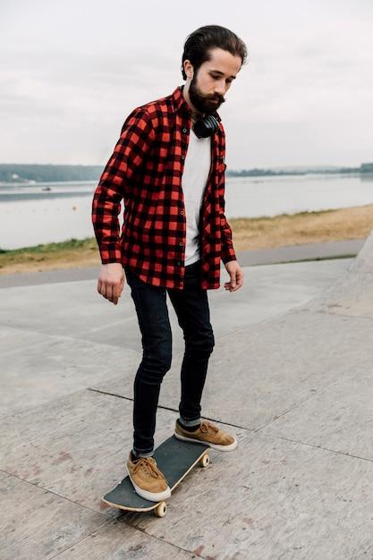 Voller schuss des mannes auf skateboard Kostenlose Fotos