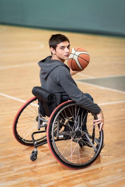 Voller schuss junger behinderter mann, der ball hält Kostenlose Fotos