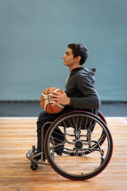 Voller schuss junger behinderter mann, der basketball hält Kostenlose Fotos