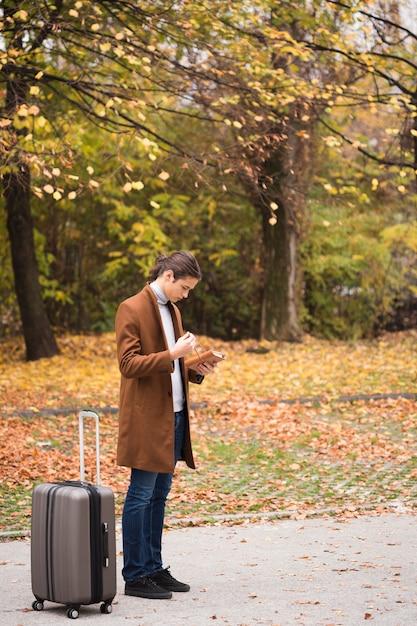 Voller schuss junger mann mit gepäck im park Kostenlose Fotos