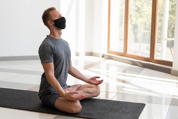 Voller schuss junger mann mit gesichtsmaske, die yoga drinnen praktiziert Premium Fotos