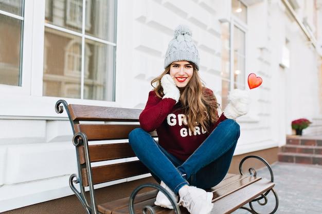 Volles lenth schönes junges mädchen mit langen haaren in strickmütze und weißen handschuhen, die auf bank in der stadt sitzen. sie hält ein karamellherz und lächelt. Kostenlose Fotos