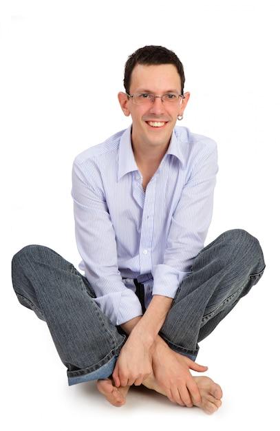 Volles porträt des lächelnden gutaussehenden mannes sitzt auf der lokalisierten flor Premium Fotos
