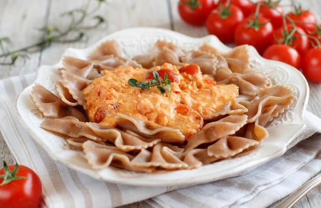 Vollkornnudeln mit stracchino-käse und frischen tomaten hautnah Premium Fotos