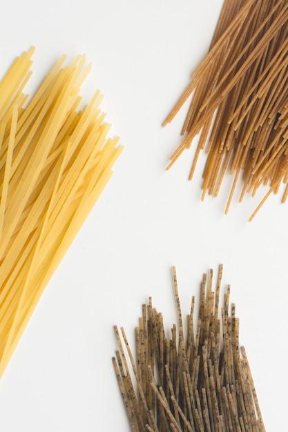 Vollkornteigwarenspaghetti tricolora auf einem weißen hintergrund Kostenlose Fotos