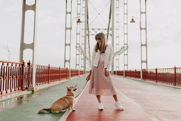 Volllanger schuss der stilvollen europäischen frau, die rosa rock und weiße jacke trägt, die mit einem corgi-hund in der sonnigen morgenstadt gehen. Kostenlose Fotos