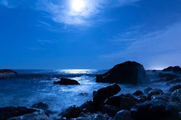 Vollmond im himmel über meerwasser Kostenlose Fotos