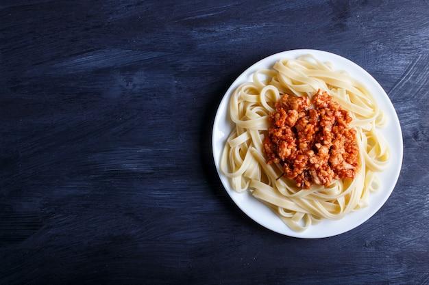 Von bolognese fettuccine-teigwaren mit hackfleisch auf schwarzem hölzernem hintergrund. Premium Fotos