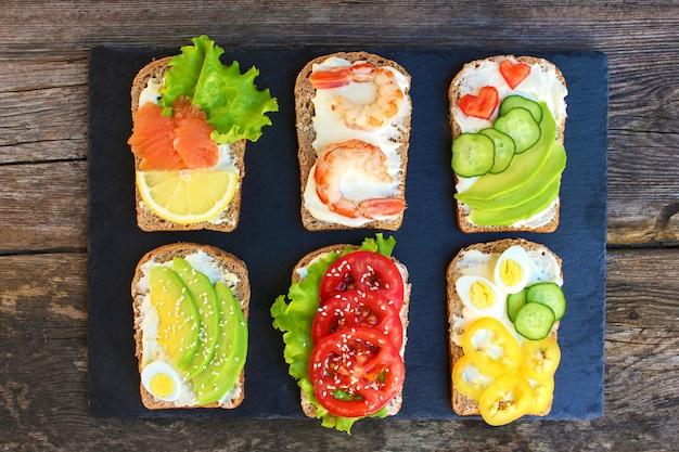 Von den verschiedenen sandwichen auf dem alten hölzernen hintergrund. ansicht von oben. flach liegen. Premium Fotos